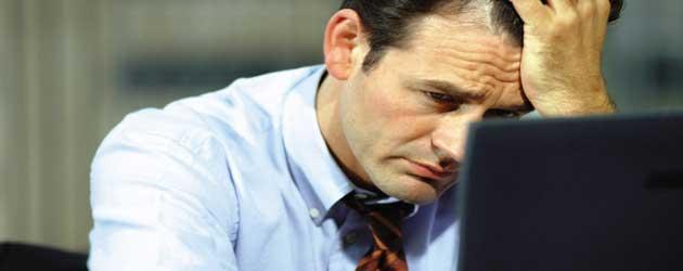 hombre delante de un ordenador con la mano en la frente y gesto ansioso