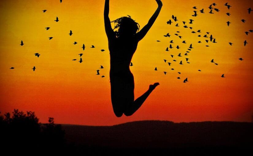 Chica saltando en un atardecer con pájaros detrás, todo haciendo sombra sobre ocre.