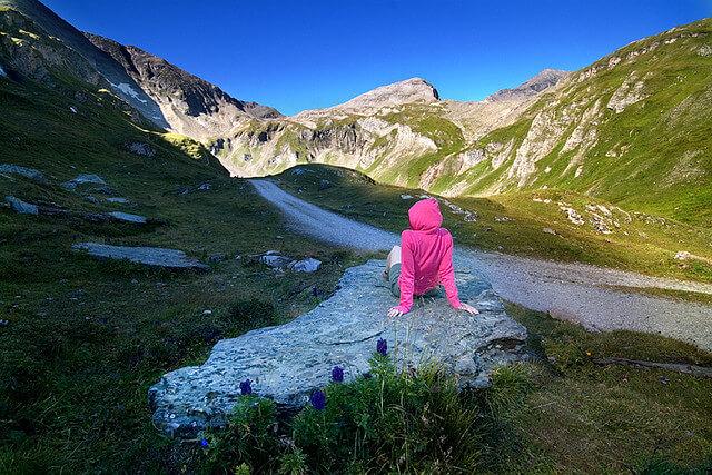 Paisaje con montañas abajo hay una chica de espaldas.