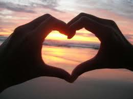 Manos formando un corazón el fondo es un atardecer en el mar.