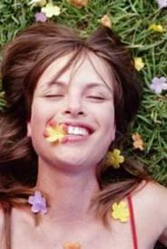 cara de chica tumbada sonriendo con flor en la boca