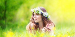 chica romántica con flores en la cabeza en la naturaleza