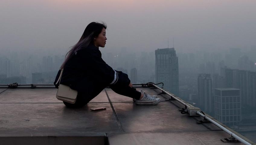 chica sentada sobre la esquina de un edificio alto se agarra las piernas pensando sobre fondo de ciudad con niebla
